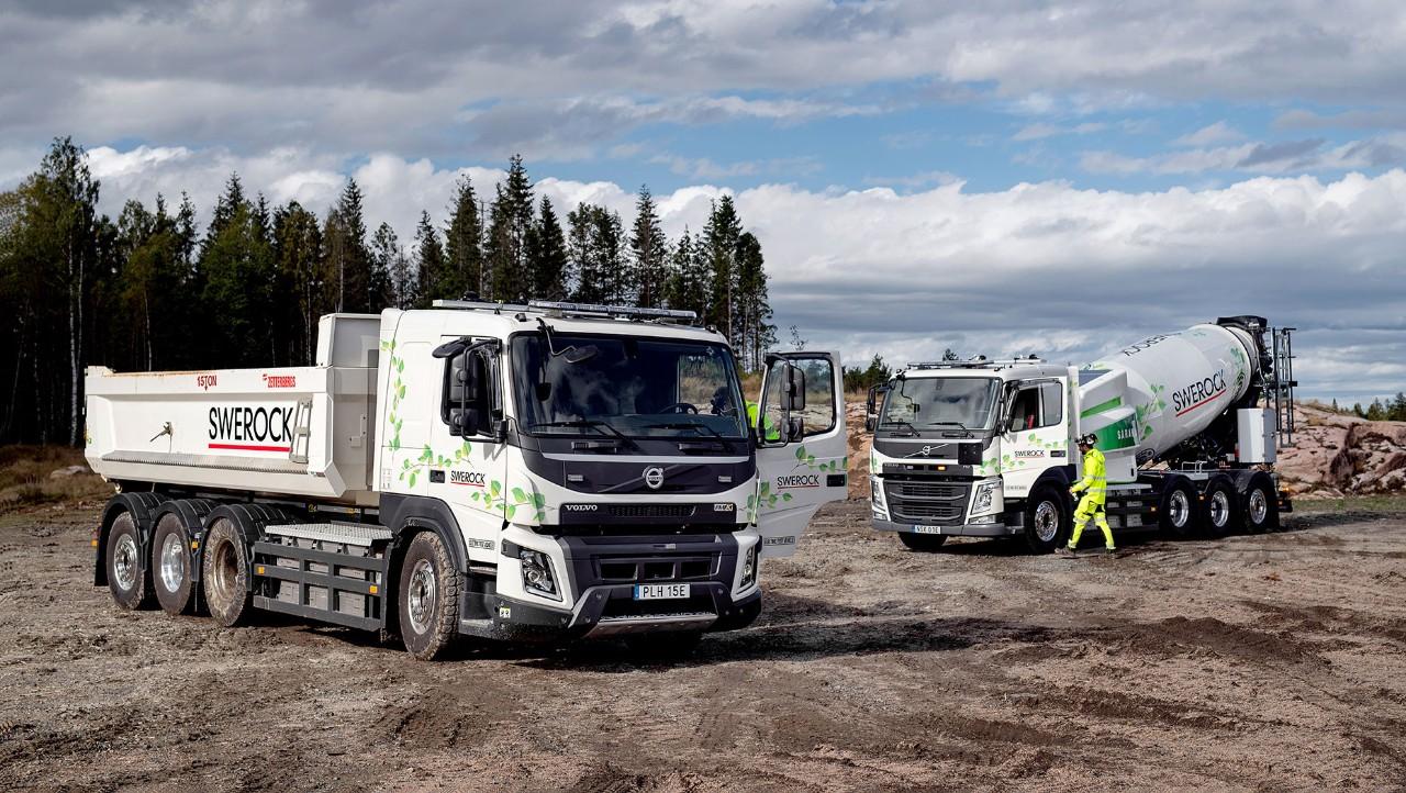 De eldrivna Volvo FM- och Volvo FMX-lastbilarna i terrängen, på lerig mark med träd i bakgrunden.