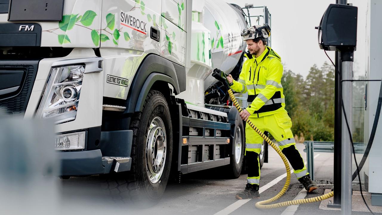 En man i varselkläder bär en laddningskabel till den eldrivna Volvo FM-lastbilen