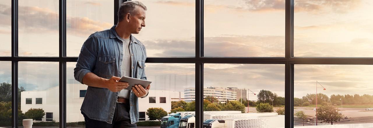 En man som håller en surfplatta står vid ett fönster och tittar ned på en lastbilsvagnpark