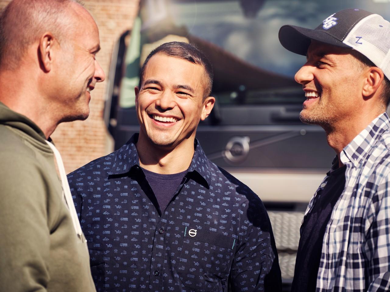 Ett närbild på tre män som ler framför en Volvo-lastbil